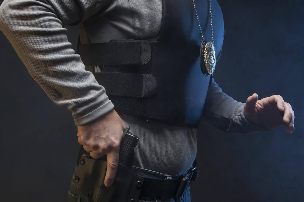 cop reaching for handgun in holster