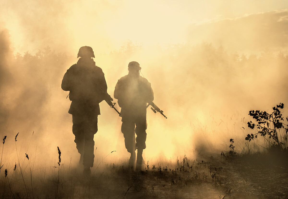 soldiers walking through a dusty battlefield