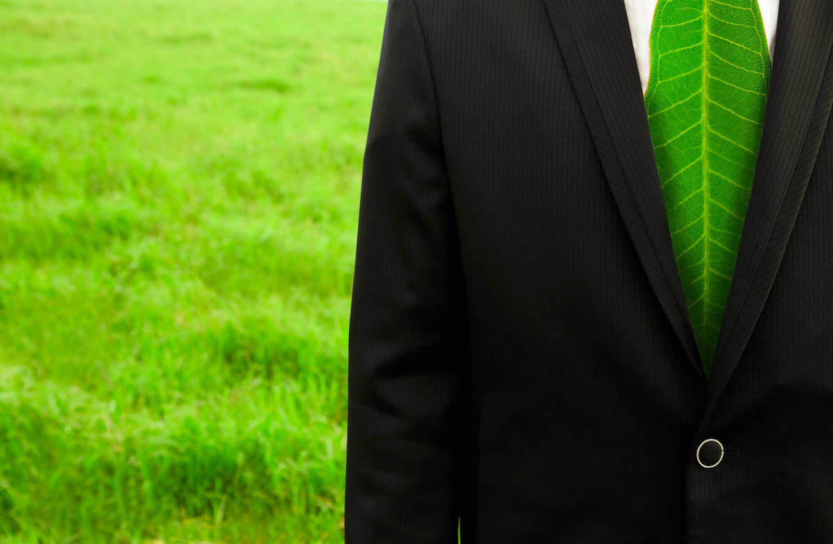 man in a suit with a leaf tie with grass behind him